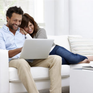 Cheerful couple relaxing together on couch surfing internet on laptop at home